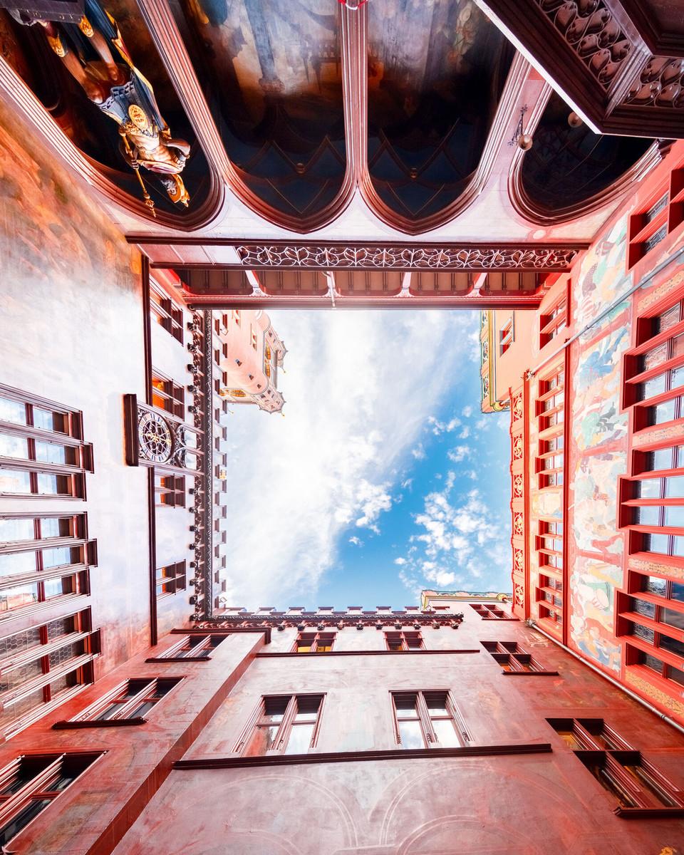 Der imposante Turm, die rote Fassade, und die verspielten Fassadenmalereien machen das Basler Rathaus zu einem Wahrzeichen der Stadt.    ///   The Town hall's red façade, characteristic tower, and playful frescoes make it an unmistakable landmark.