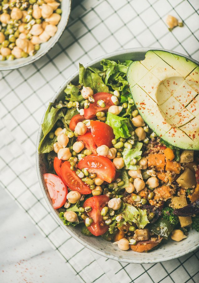 Vegan lunch bowl. Flat-lay of vegan dinner with avocado, mixed grains, beans, sprouts, greens and vegetables, top view. Vegan, vegetarian, clean eating, healthy diet food concept