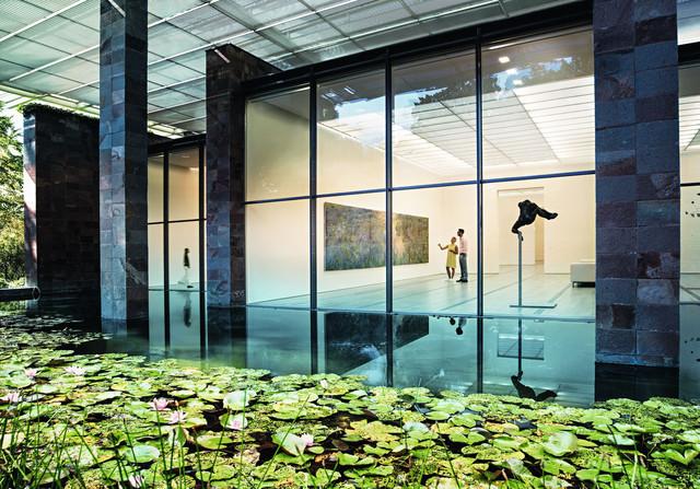Die Fondation Beyeler in Riehen. Zentral sind Besucher zu sehen, welche das Bild Le Bassin aux nymphéas von Claude Monet betrachten, im Vordergrund der Teich mit Seerosen.