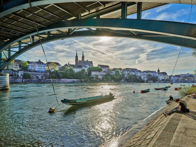 Rheinpanorama Aufnahme am Nachmittag vom Oberen Rheinweg aus, unter der Wettsteinbrücke. Zentral ist der Weidling 'Fischerin' zu sehen, dahinter das Basler Münster.