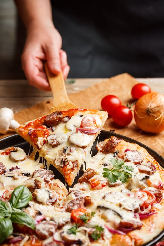 Pizza topped with cheese, sausage and cherry tomato