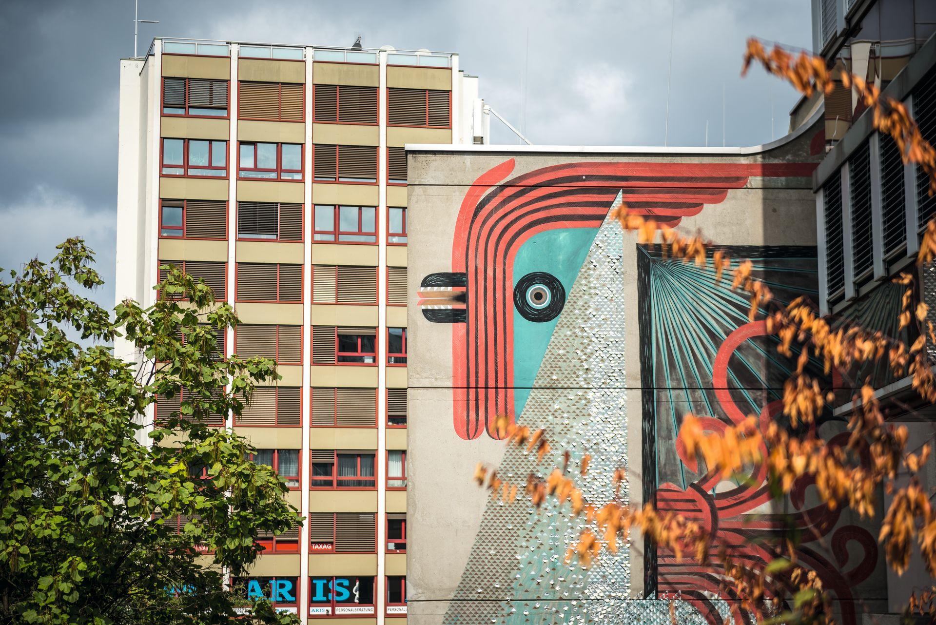 L'artiste suisse de graffiti et de street art Tika s'est fait un nom à l'international avec des peintures de grandes dimensions. Ici, à Heuwaage, elle a peint un immense coq aux couleurs éclatantes, ou plus exactement un basilic, l'animal héraldique qui figure sur le blason de Bâle.